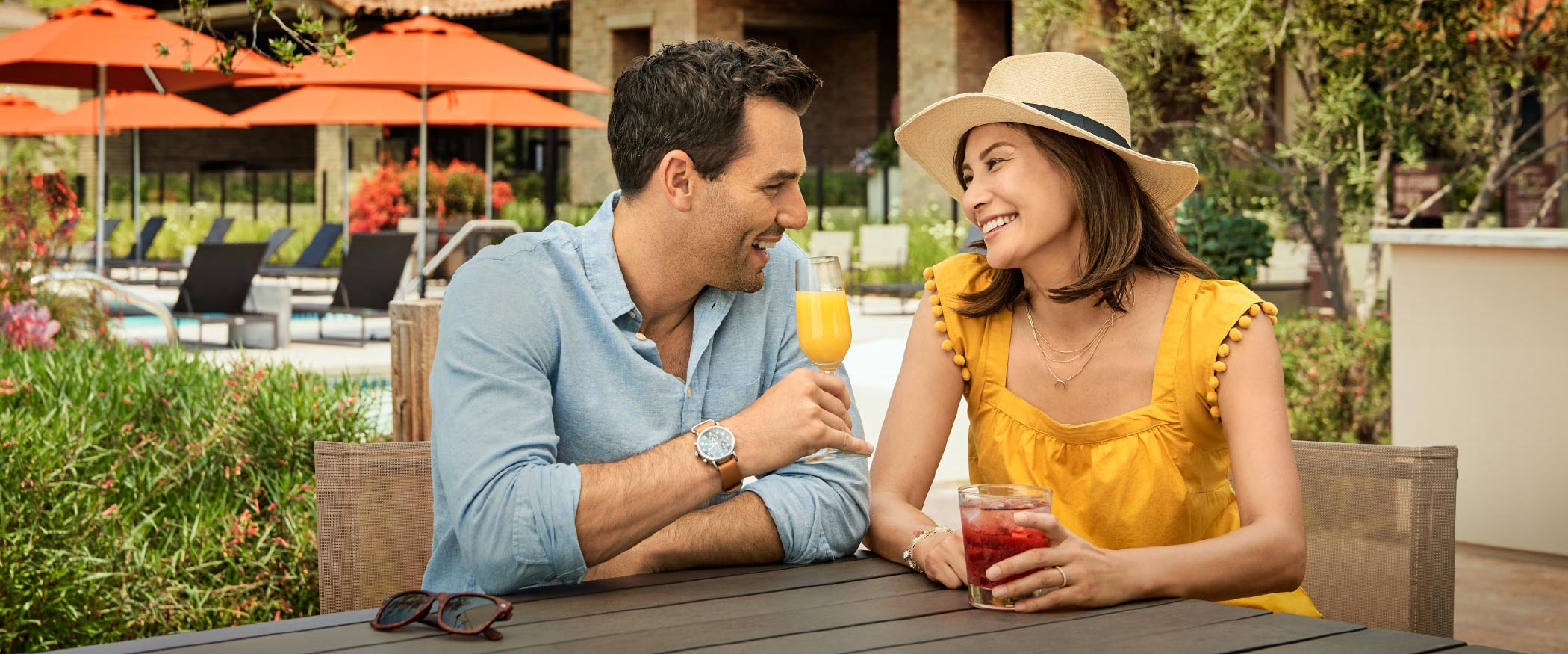 Couple enjoying cold drinks by the pool