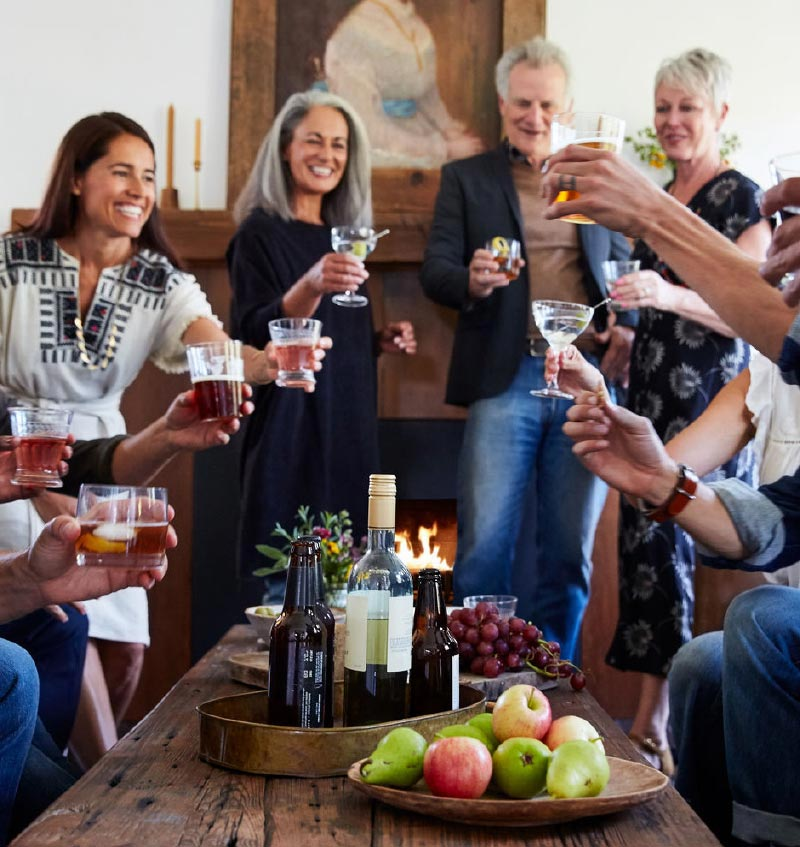 Group of friends toasting by a fireplace